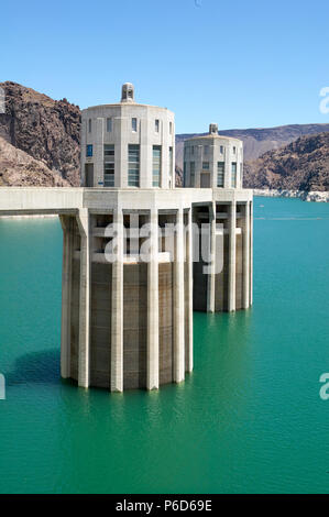 Two of the intake towers on the Hoover dam on the Colorado River in Black Canyon in a picturesque view across the water - Stock Photo