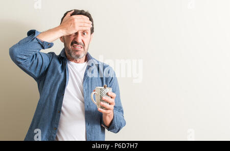 Senior man drinking coffee in a mug stressed with hand on head, shocked with shame and surprise face, angry and frustrated. Fear and upset for mistake - Stock Photo