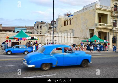 Blue vintage cars passing a street party on Malecon Street in Havana, Cuba, balloons, coast, quay, people, music, vacation, old house facades - Stock Photo