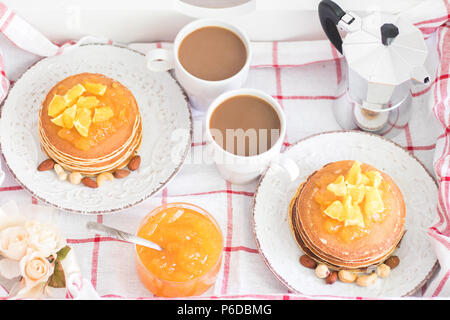 Romantic traditional breakfast for two on a tray. American pancakes with orange jam and nuts on vintage plates and 2 white coffee cups with italian me - Stock Photo