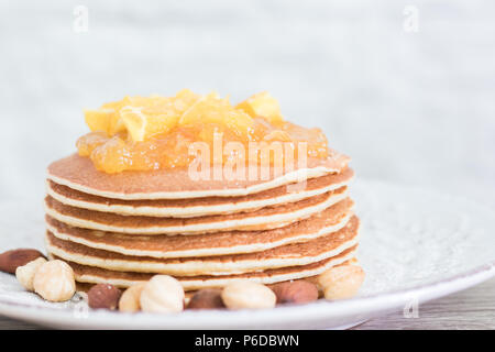 Stack of freshly backed pancakes on a vintage plate with nuts and orange jam on top. Front view. Copy space - Stock Photo