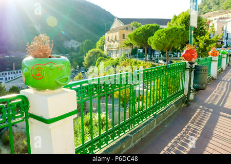 Vietri sul Mare Summer colourful cityscape with funny ceramic flower pots faces on fence and mountains. Italy, Amalfi coast - Stock Photo