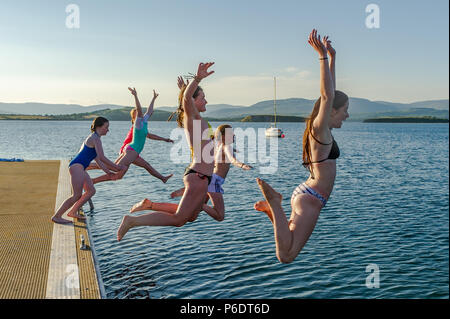 Bantry, West Cork, Ireland. 29th June, 2018. After a scorchingly hot day during the current heatwave, a group of young girls jump into the sea from a pontoon as the sun goes down in Bantry. The rest of the weekend will be cooler than previous days with rain forecast for next week. Credit: Andy Gibson/Alamy Live News. - Stock Photo