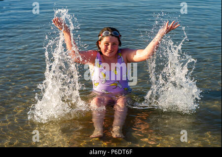 Bantry, West Cork, Ireland. 29th June, 2018. After a scorchingly hot day, 11 year old Nora Fox from Bantry plays in the water as the sun goes down in Bantry. The rest of the weekend will be cooler than previous days with rain forecast for next week. Credit: Andy Gibson/Alamy Live News. - Stock Photo