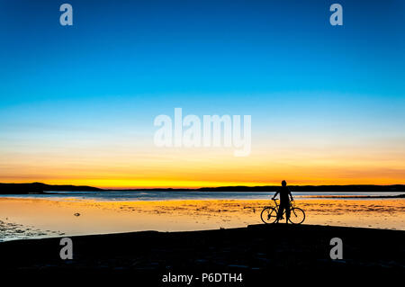 Ardara, County Donegal, Ireland weather. 29th June 2018. A cyclist watches the sunset on Ireland's 'Wild Atlantic Way' at the end of a hot summer day on the north-west coast. Credit: Richard Wayman/Alamy Live News - Stock Photo