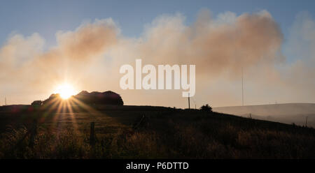 West Pennine Moors , UK, 29 June 2018. The evening sun shines through the smoke from the fires on the West Pennine Moors at Winter Hill. Winter Hill television mast can be seen through the smoke from the nearby fires. - Stock Photo