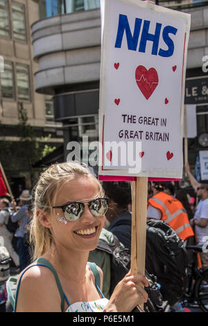 London, UK. 30 June, 2018. A woman smiles at the camera with her placard held high. With the NHS 70 years old this year, thousands marched through central London in a National rally to show support for the service and to demand more funding from the Government. David Rowe/Alamy Live News - Stock Photo