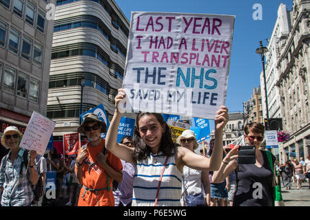 London, UK. 30 June, 2018. London,UK. A Young woman holds up her placard which reads ' Last year I had a liver transplant, the NHS saved my life'. With the NHS 70 years old this year, thousands marched through central London in a National rally to show support for the service and to demand more funding from the Government. David Rowe/Alamy Live News - Stock Photo