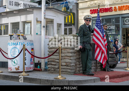 During the 'Cold War' Checkpoint Charlie used to be one of the most famous border crossings in the world. Nowadays it is a major tourist attraction in - Stock Photo