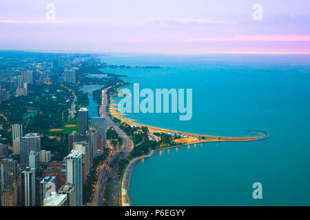 View of Chicago Illinois and Lake Michigan with beaches, buildings and roads in view at sunset - Stock Photo