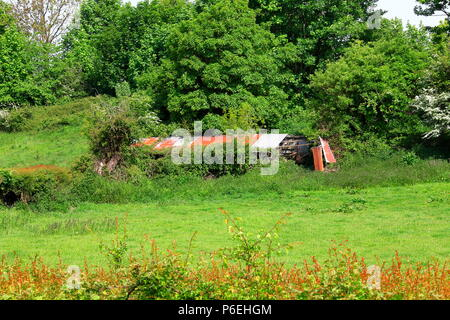 A decaying old animal shelter at the side of a field made of wood and galvanized steel sheets which has fallen into disrepair and decay. - Stock Photo