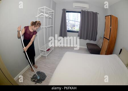 Asian female maid Cleaning Service with Mop cleaning floor on a bedroom. - Stock Photo