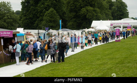Large crowd of people at showground, walking near entrance, past trade stands & exhibits at busy RHS Chatsworth Flower Show, Derbyshire, England, UK. - Stock Photo