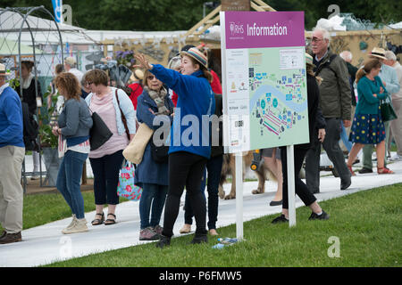 RHS volunteer working by large information board map, pointing, directing & guiding female showground visitor - Chatsworth Flower Show, Derbyshire, UK - Stock Photo
