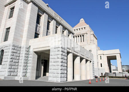 The unique, classic granite central tower of the National Diet Building of Japan, the meeting place of the national government, rises into a blue sky - Stock Photo