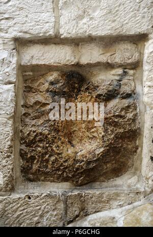 Israel. Jerusalem. Old City. Old City. V Station. Place of encounter between Jesus and Simon of Cyrene, the man who carried the cross of Christ to Mount Calvary. Detail of the stone from 1st century, where it's said that Jesus left the print of his hand. - Stock Photo