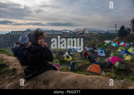 Refugee children are sitting on the hill and watching life at the makeshift camp of the Greek-Macedonian border near the Greek village of Idomeni. - Stock Photo