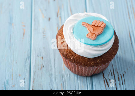 Tasty cake on blue wooden table, thumb up - Stock Photo