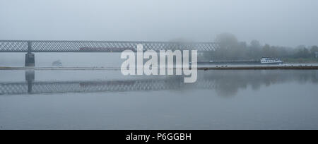 Foggy autumn morning in Germany on the river Rhine, a flowing barge in the distance an old railway bridge. - Stock Photo