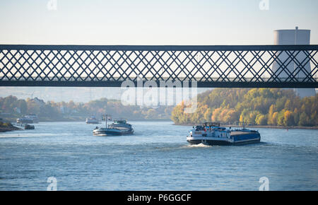 Sunny autumn day in Germany on the river Rhine. The barge flows under the railway bridge. A visible chimney of a nuclear power plant. - Stock Photo
