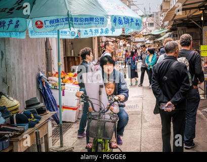 19 February 2018 - Lantau Island, Hong Kong. Asian woman cycling in the village street of Tai O with child on the bike. - Stock Photo