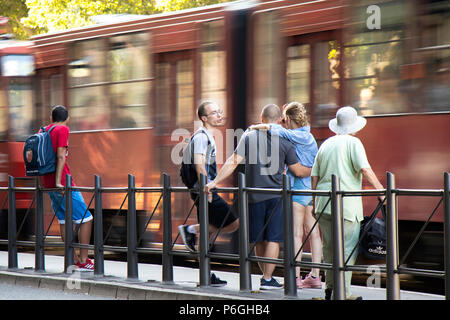Belgrade, Serbia - June 1, 2018 : People standing at a bus stop and waiting for public transportation on a sunny spring day with blurry motions and re - Stock Photo
