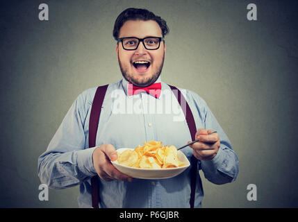 Young excited man having a plate of potato chips