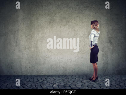 Side view of businesswoman standing in front of gray wall and contemplating in effort to solve problem - Stock Photo