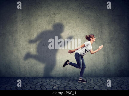 Woman running away from her fat shadow on the wall. Body weight control concept - Stock Photo