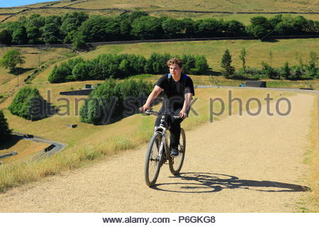 A Boy Rides His Mountain Bike In The Early Evening Sun At Dove Stone Reservoir, Greenfield, Saddleworth, Oldham Summer June 2018 - Stock Photo