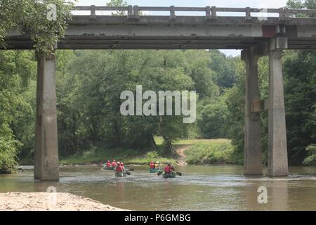 Canoers Crossing Under A High Bridge - Stock Photo