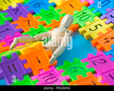 Wooden puppet sit behind colorful plastic number on blue background. Concept of education - Stock Photo