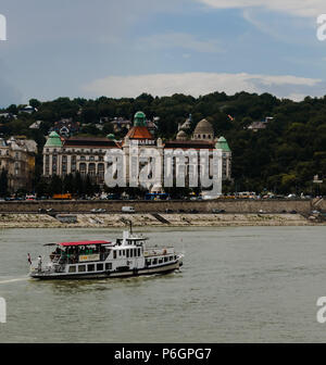 A ship on the Danube river in front of the Gellert baths. In the background there is the Gellert mountain. - Stock Photo