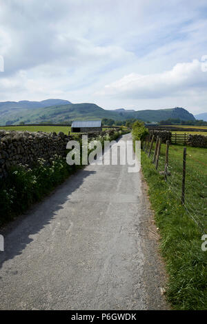 tarmaced country lane bounded by dry stone wall and wire fence in rural underskiddaw keswick cumbria england uk - Stock Photo