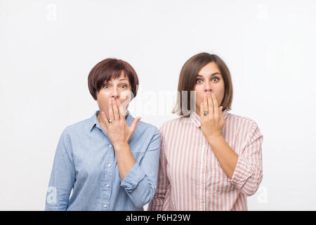 Portrait of a two surprised women mature mother and daughter standing over gray background and - Stock Photo