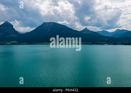 Lake called Wolfgangsee in Austria with Mountains in the Background and Clouds on the Sky - Stock Photo