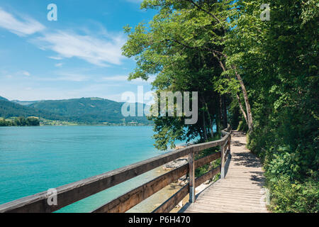Jetty on the edge of the turquoise lake called Wolfgangsee mountains in the background and clouds on the sky - Stock Photo