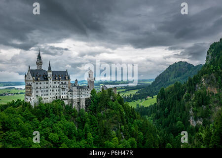 Castle Called Neuschwanstein with much trees and mountains in the background in bavaria - Stock Photo