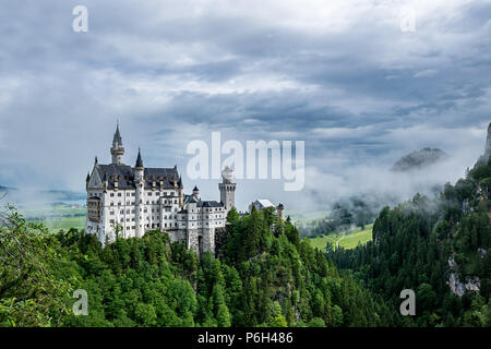 Castel called Neuschwanstein in bavaria with clouds on the sky and a little fog on a sunny day - Stock Photo