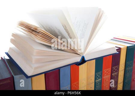 stack of colored books on white desk closeup - Stock Photo