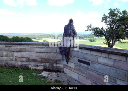 Monk Maurus with a violin sitting on the wall around the church of St. James in Hohenberg, Germany - Stock Photo