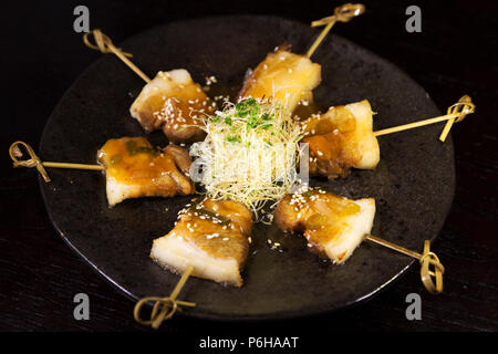 Grilled pork belly served on skewers. The dish features Asian spices.. - Stock Photo