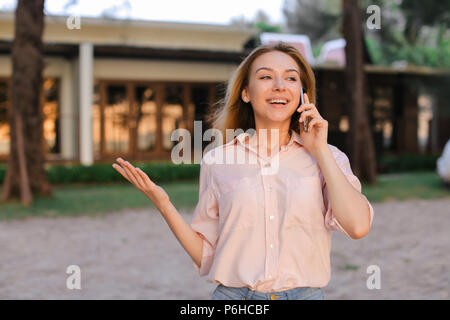 Young female person talking by sartphone outside, wearing blouse. - Stock Photo