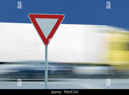 Give way yield text road sign and truck traffic in the motion blurred background - Stock Photo
