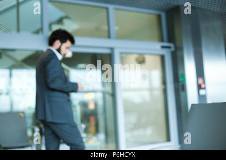 Caucasian businessman going at office, wearing grey suit. - Stock Photo