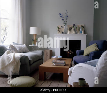 White and blue armchairs and a grey sofa seta around a low wooden coffee table in front of the fireplace in a white living room - Stock Photo