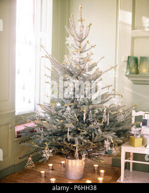 Ring of candles around a Christmas tree decorated with artificial frost and glass stars in corner of dining room - Stock Photo