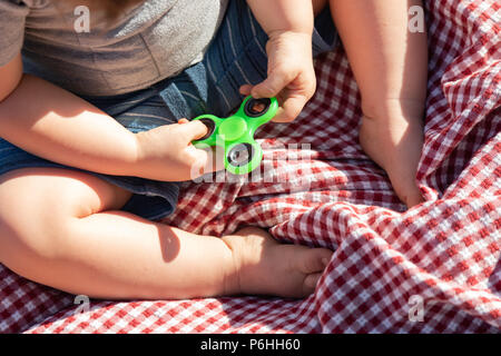 Baby Boy Sitting on Picnic Blanket Playing With Fidget Spinner - Stock Photo