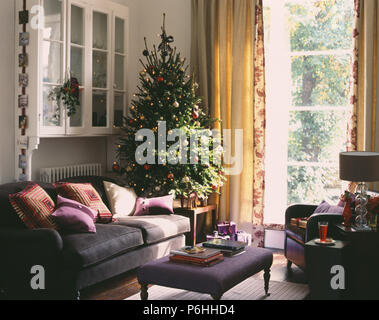 White glass-front cupboard on wall above grey sofa and decorated Christmas tree in living room with cream curtains - Stock Photo