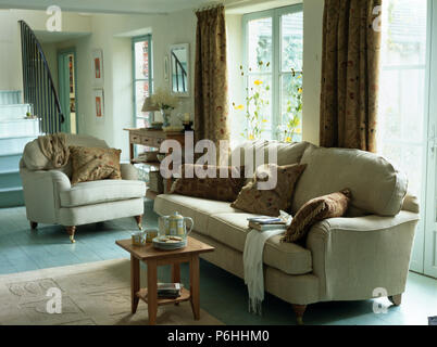 Cream sofa and armchair with brown cushions in country living room with tea set on small wooden stool - Stock Photo